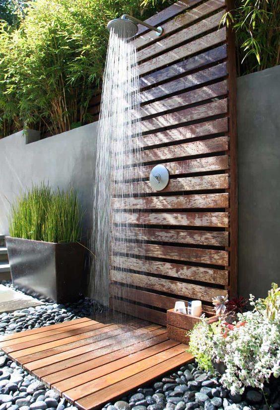 een houten tuindouche in een moderne tuin et hout en grote kiezels