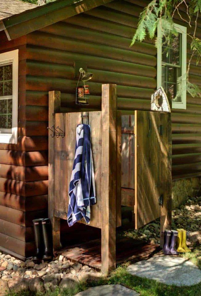 Prive douchehokje in de tuin naast een blokhut
