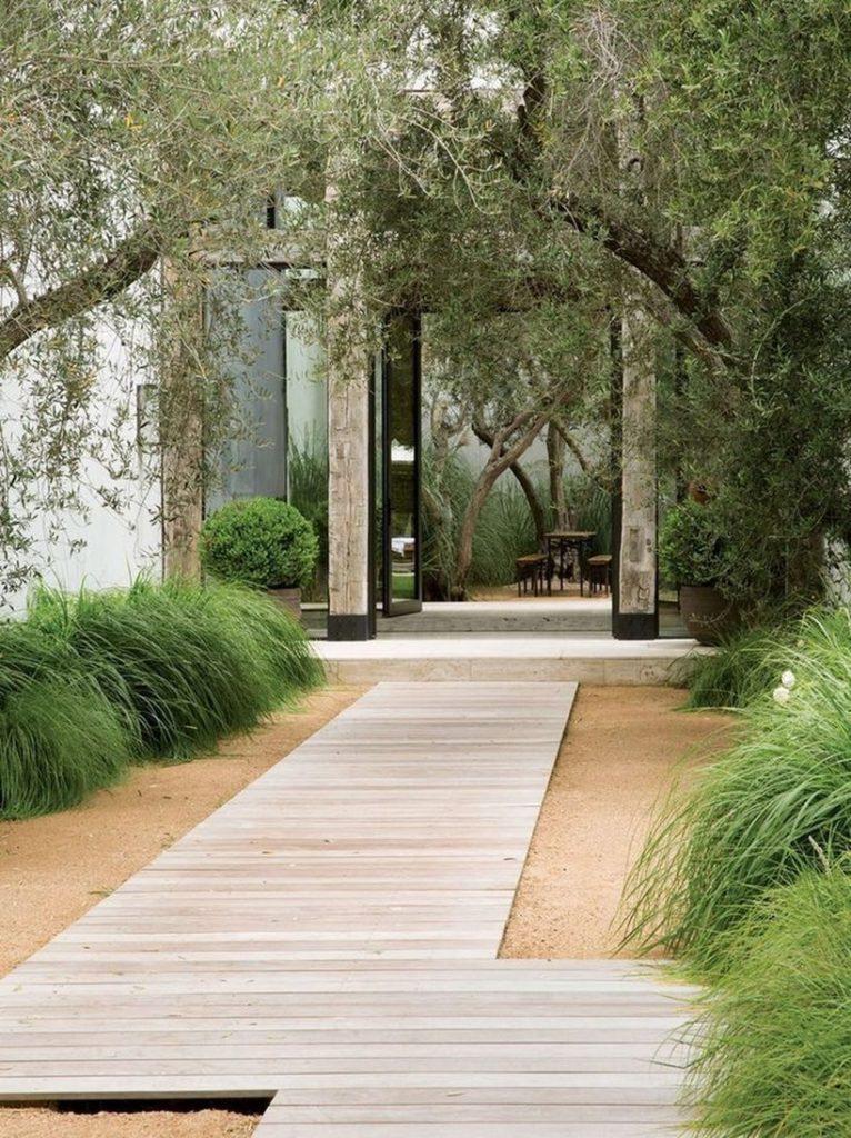 voortuin ontwerp met strakke houten pad  met grind naar de voordeur.