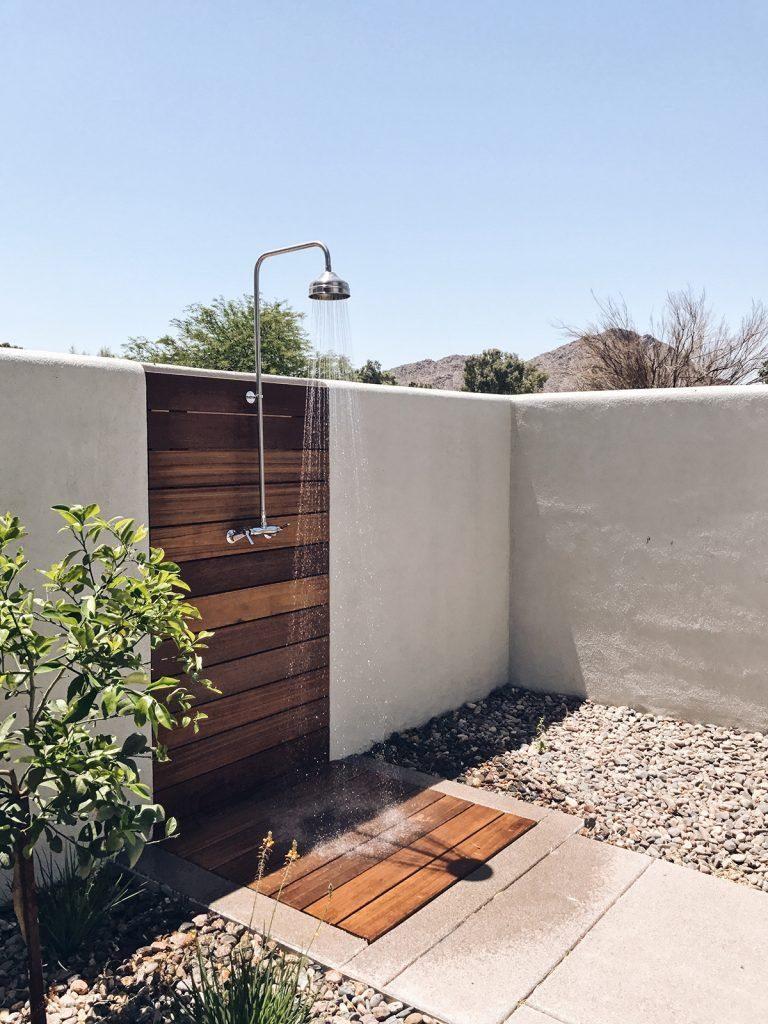 moderne buitendouche van hout met een witten muur