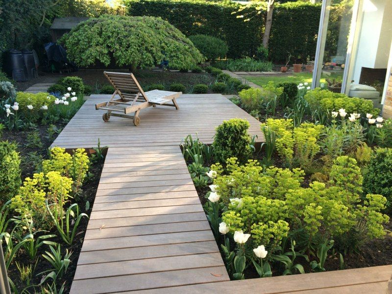 houten vlonder met beplanting en een tuinmeubel