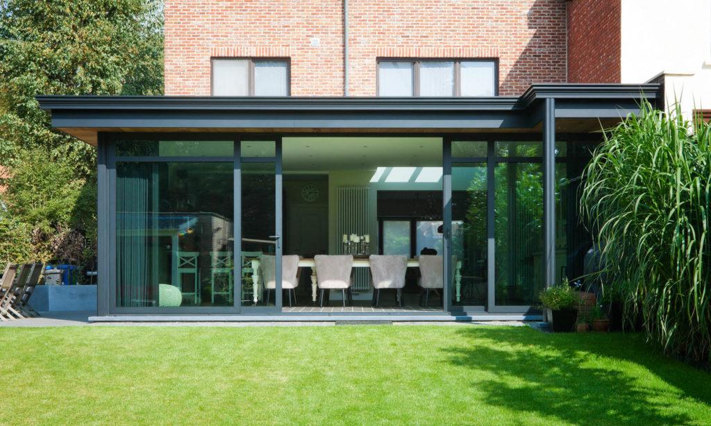 een moderne veranda van glas met een schuifpui