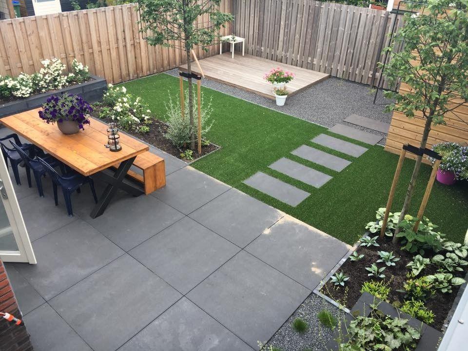 strakke bestring in een moderne tuin met een stuk gras en tuinmeubelen