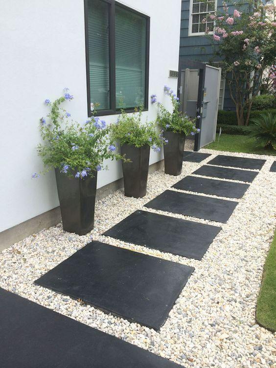 een pad met grote tuintegel en grind