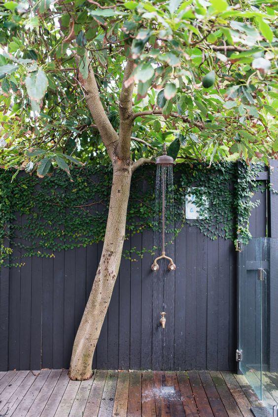 zwarte schutting met een boom en tuindouche