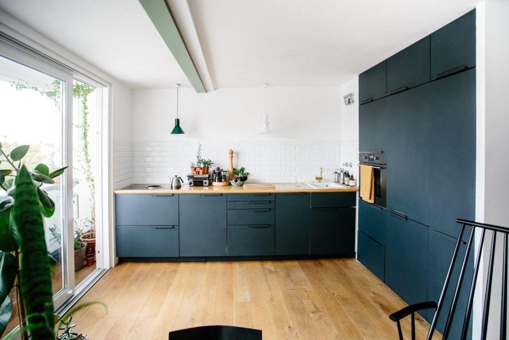 donkergroene keuken met grote kastenwand