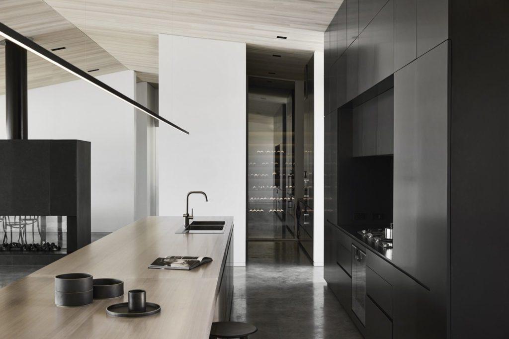strakke zwarte moderne keuken met greeploze keukenkastjes