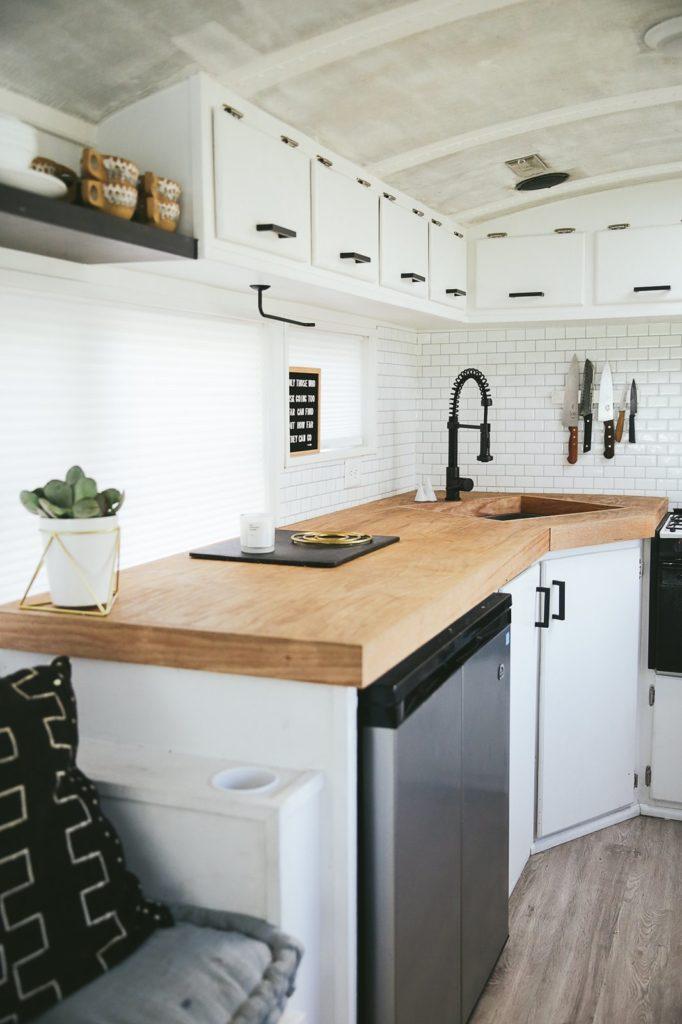 kleine witte landelijke keuken met zwarte kraan