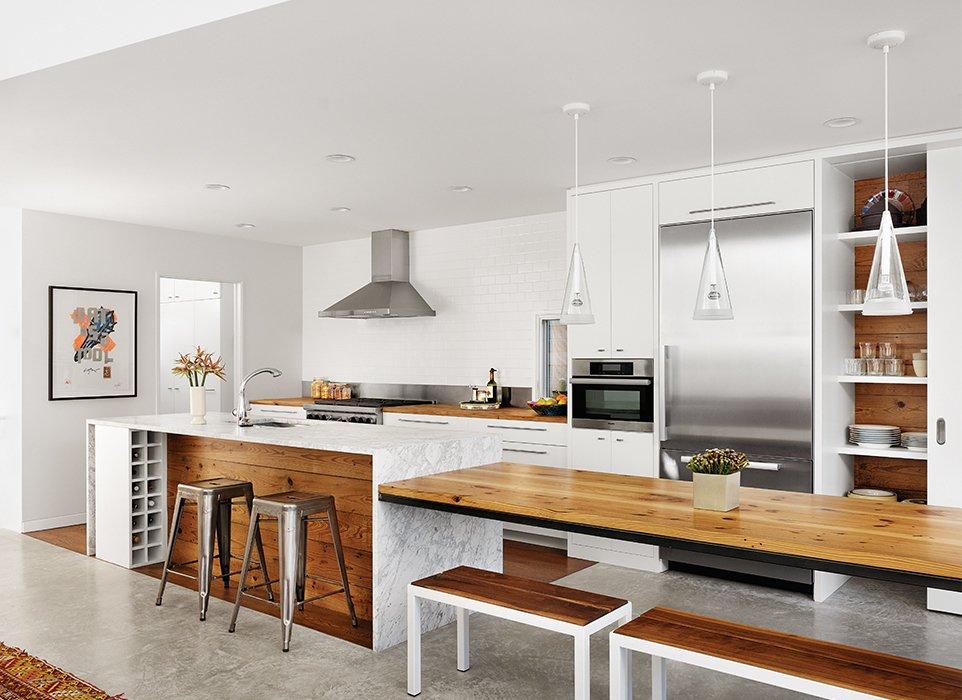 lichte moderne keuken met kookeiland van marmer en tafel in het verlengde