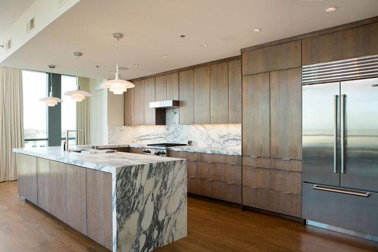 Marmer aanrechtblad met houten keukenkasten en grote amerikaanse koelkast