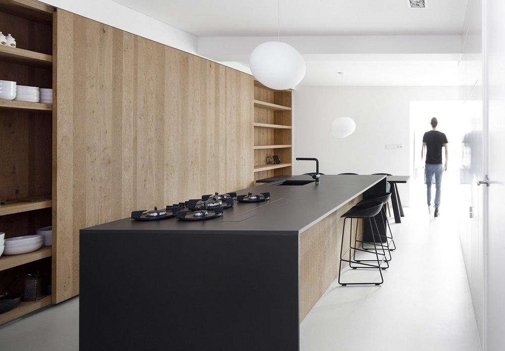 strakke greeploze keukenkastjes van hout met kookeiland met gasfornuis