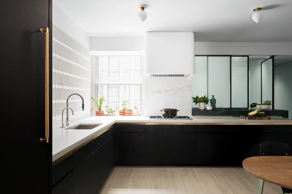strakke greeploze keukenkastjes met marmer aanrechtblad en spatwand met gouden accessoire