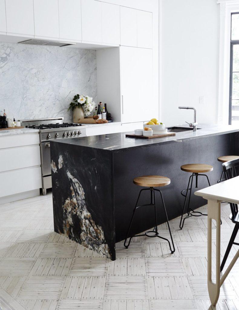 Strakke greeploze witte keukenkastjes met donkere natuurstenen keuknblad