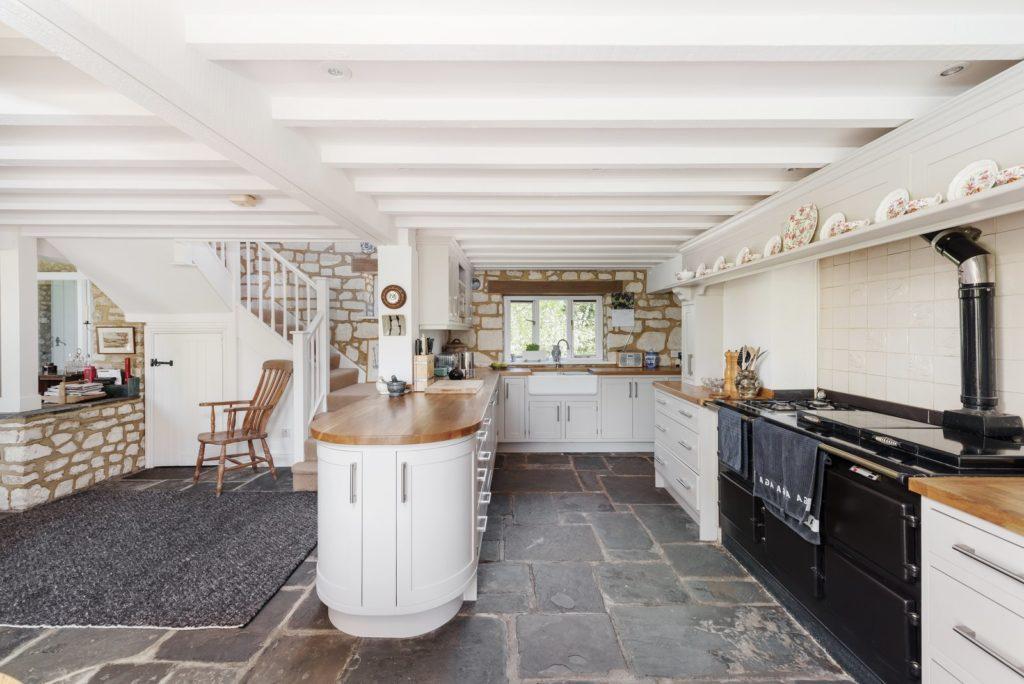 Landelijke schiereiland keuken met stenen vloer