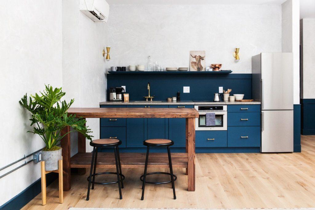 blauwe keukenkastjes en houten bartafel
