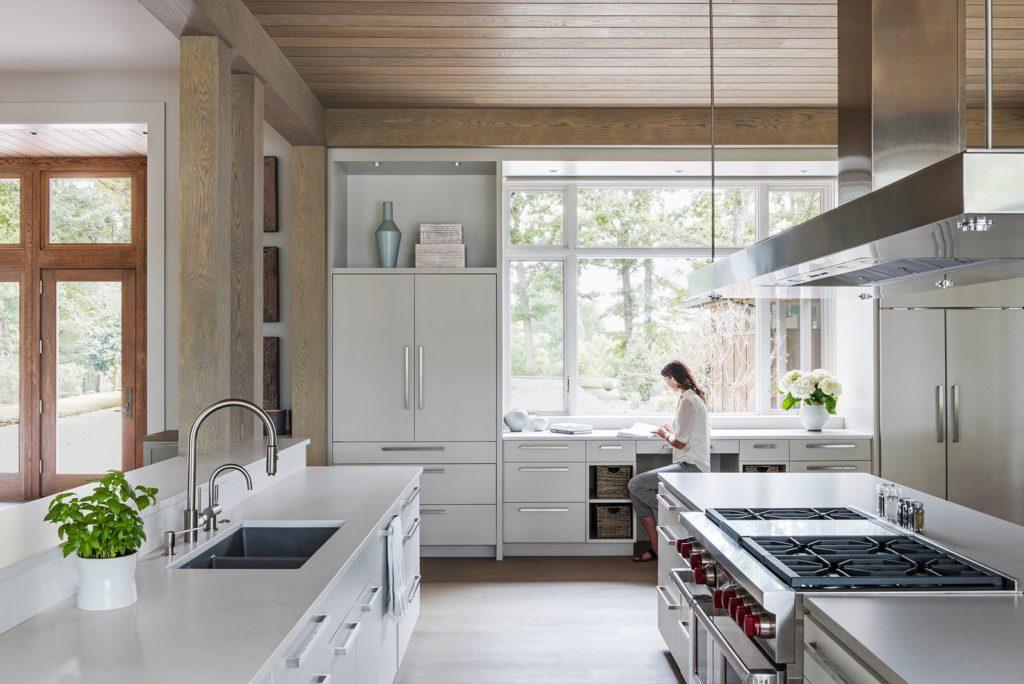 witte keukenkastjes met rechte grepen en afzuiger boven schiereiland