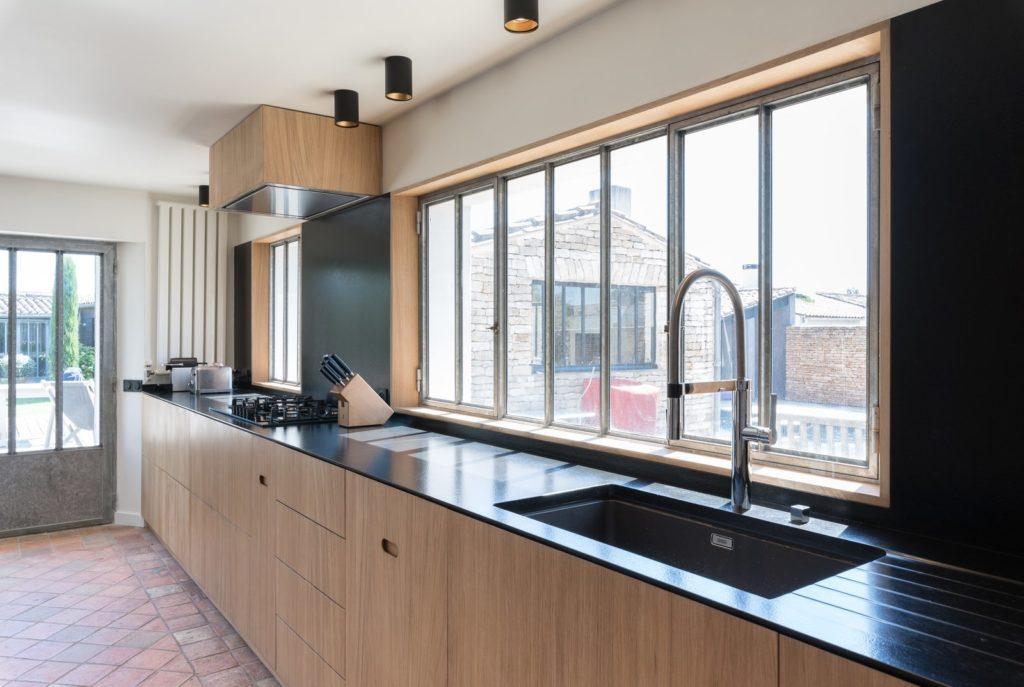 Lange wand met keukenkastjes en wastafel houtkleurig met zwart