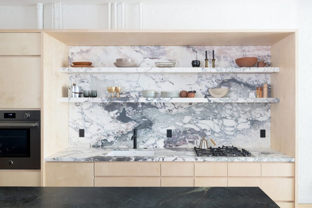 marmer spatwand en lichte houten keukenkastjes