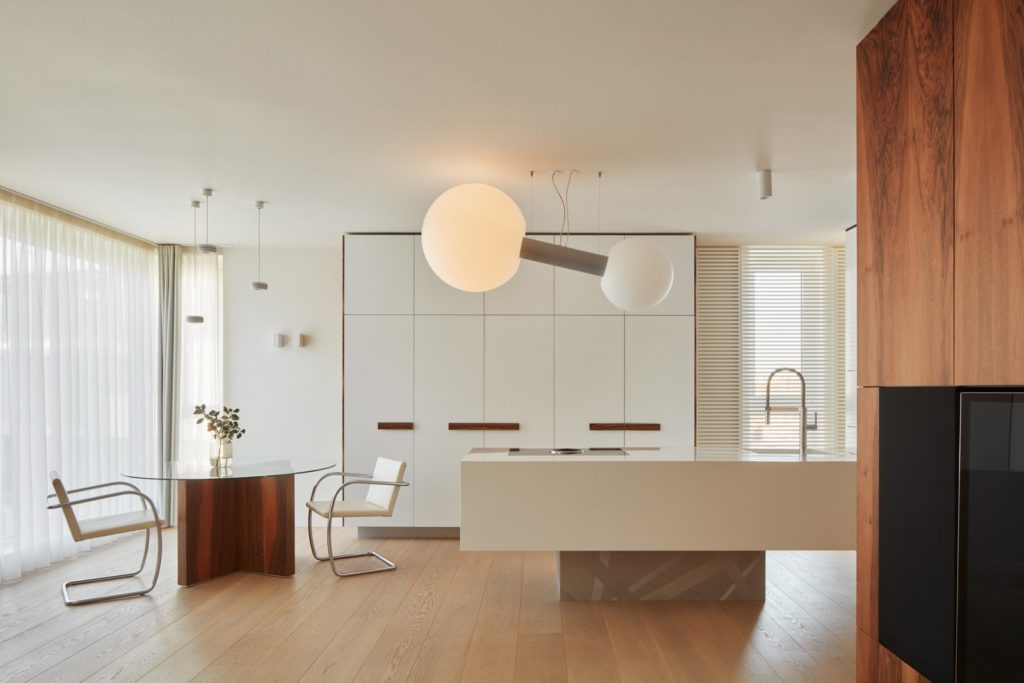 strak kookeiland en witte greeploze keukenkastjes