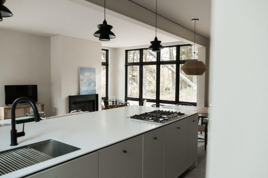 grijze keukenkastjes met wit hoogglans aanrechtblas met gasfornuis