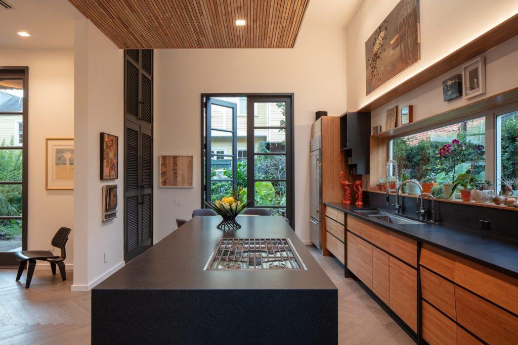 Zwart aanrechtblad en houten keukenkastjes