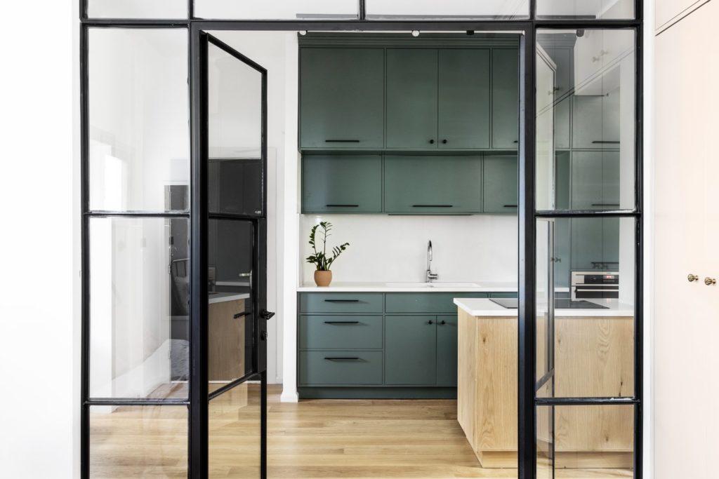 zwarte glazen deur naar olijf groene keukenkastjes