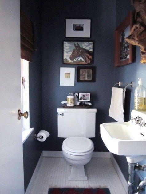 blauw landelijk toilet met fotolijstjes en kunst aan de muur