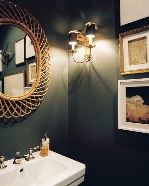 groen toilet ideeën met gouden accessoires en fotolijstjes op de muur
