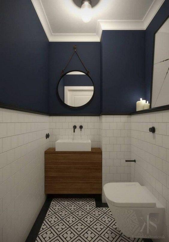 modern blauw toilet met witte onderwand en ronde spiegel