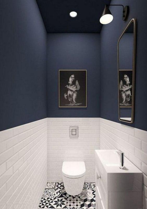 modern blauw toilet met witte onderwand en gouden fotolijst en spiegel