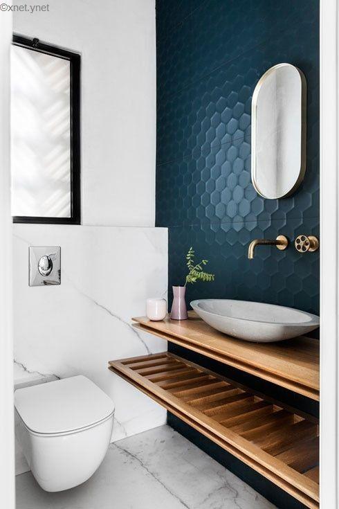 modern blauw toilet met moderne wasbak en gouden kraan uit de muur