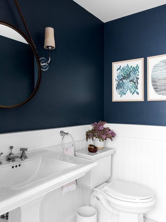 modern blauw toilet met fotolijsten en witte onderwand