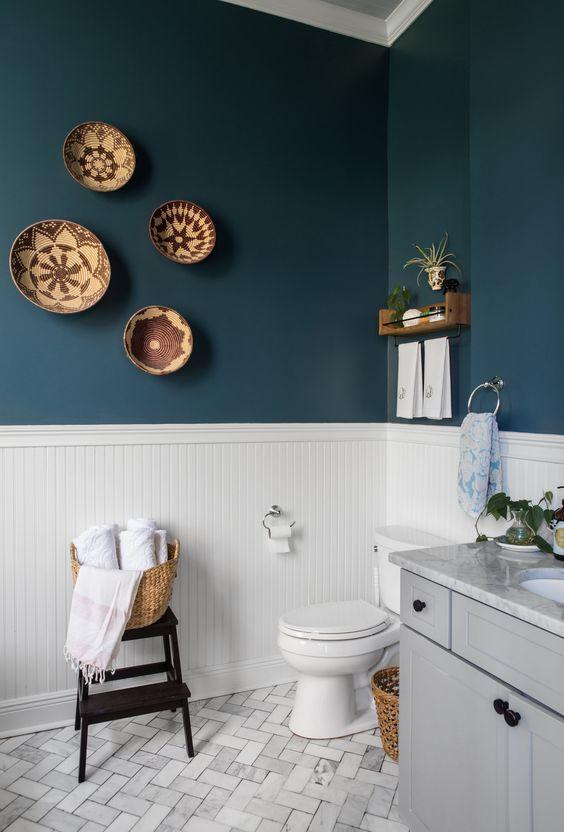 blauw modern landelijk toilet met decoratie aan de muur een witte wand en lichtgrijs meubel
