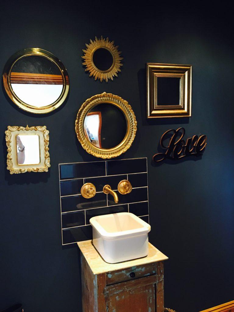 modern blauw toilet met gouden spiegels en fotolijsten