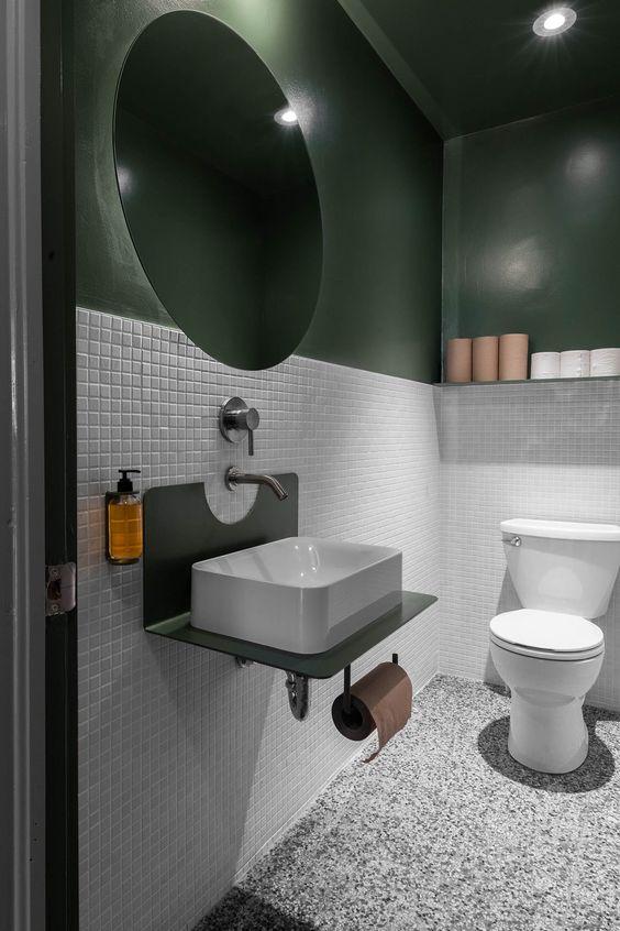modern groen toilet met witte onderwand van mozaic tegels en grote ronde spiegel