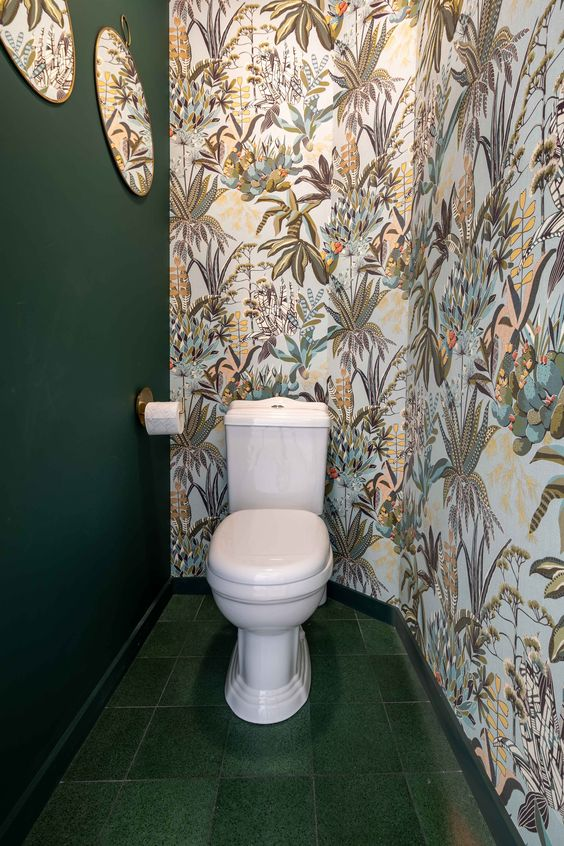 modern groen toilet met behang van bladeren en ronde spiegel