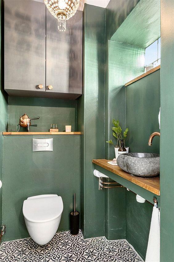 modern pastel groen toilet met gouden accessoires en tegels met patroon