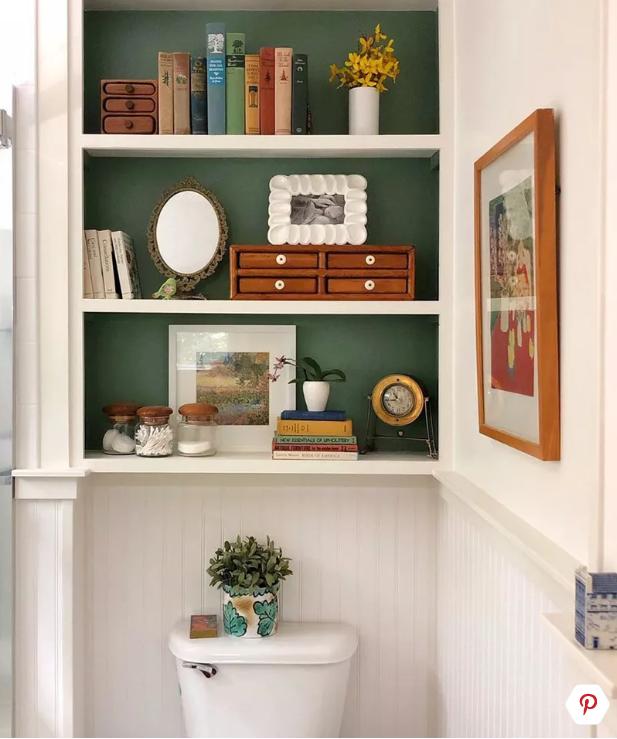 toilet met groene achterwand met boeken en accessoires
