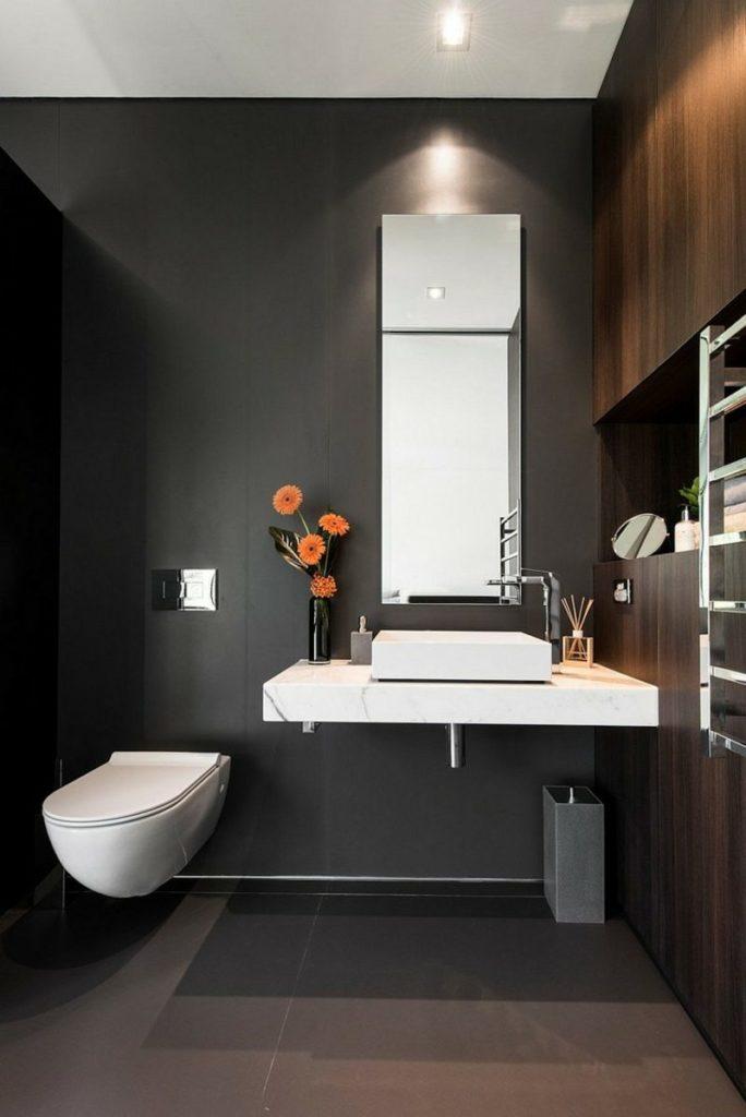 modern zwart toilet met witte marmer wastafel en houten wand