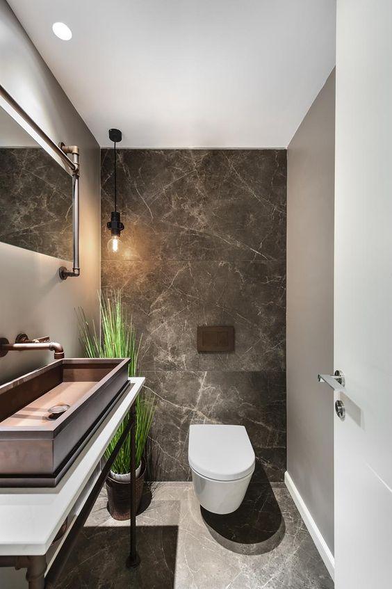 zwarte natuurstenen toilet met grote tegels en modern wastafel