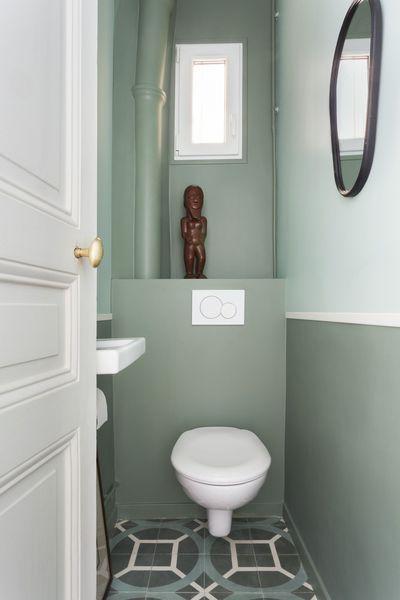 rustig pastel groen toilet met houten man