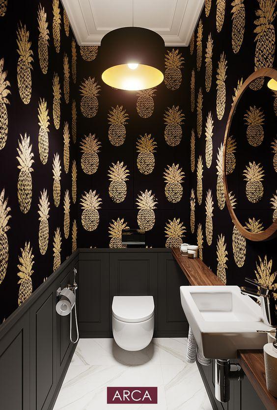 zwart toilet met witte marmer vloer en behang van gouden ananassen