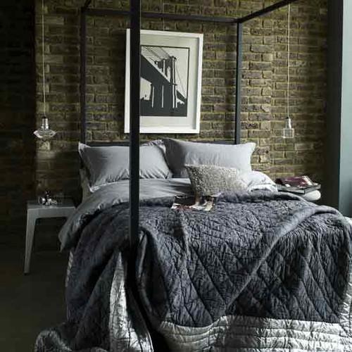 grijze stenen muur in modern industriele slaapkamer met groot stalen bedframe