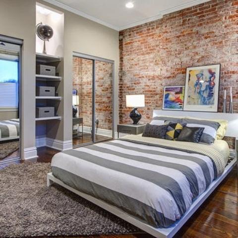 rode stenen muur in moderne slaapkamer met laag bed en kasten en grote spiegel met schuifdeur