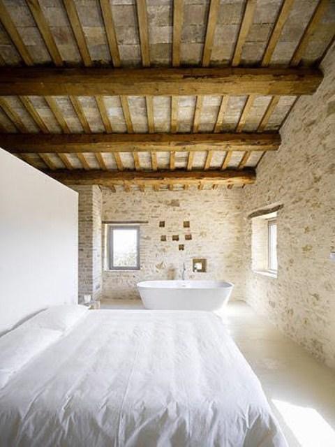 lichtgrijze stenen muur in open landelijke slaapkamer met bad in slaapkamer