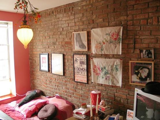 rode stenen muur in moderne slaapkamer met fotolijstjes en roze dekbed