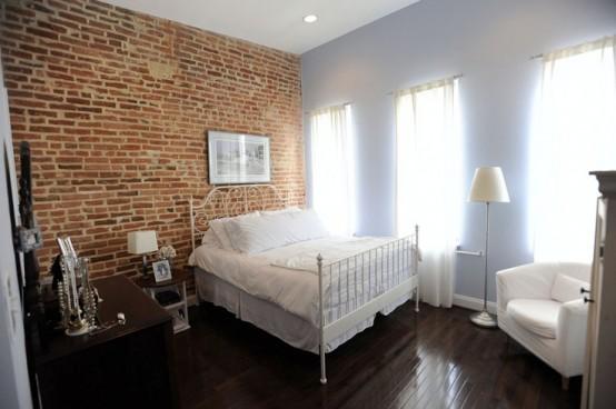 bakstenen muur in landelijk moderne witte slaapkamer met staal bed en hoge ramen