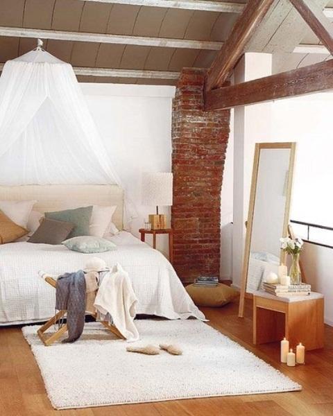 stenen pilaar met houten balk in oude lichte industriele slaapkamer