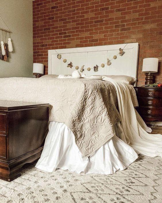 rode stenen muur in moderne slaapkamer met groot wit bed en beige plaid