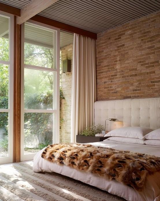 bakstenen muur in moderne slaapkamer met groot wit bed en lekker vloerkleed